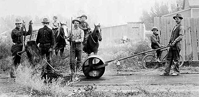 Laying sidewalk in Rifle, Garfield County, Colorado circa 1905.  Men work with rakes, a wheelbarrow, tar, and a roller. Boys on horses or a bicycle look on.  Date [between 1905 and 1915?] Call Number X-13183.  Formerly F28425.   Hyperlink to Denver Public Library.